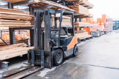 forklift machine standing at wooden planks on shelves outside