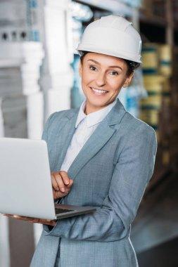 Female inspector in helmet with laptop in warehouse stock vector