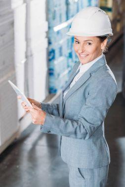 Female inspector in helmet using digital tablet in storage stock vector