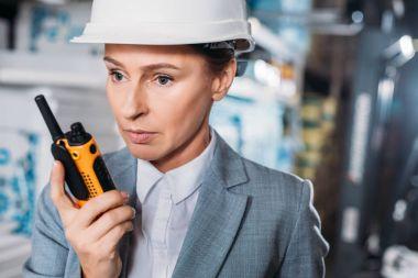 Female inspector in helmet with walkie talkie in warehouse stock vector
