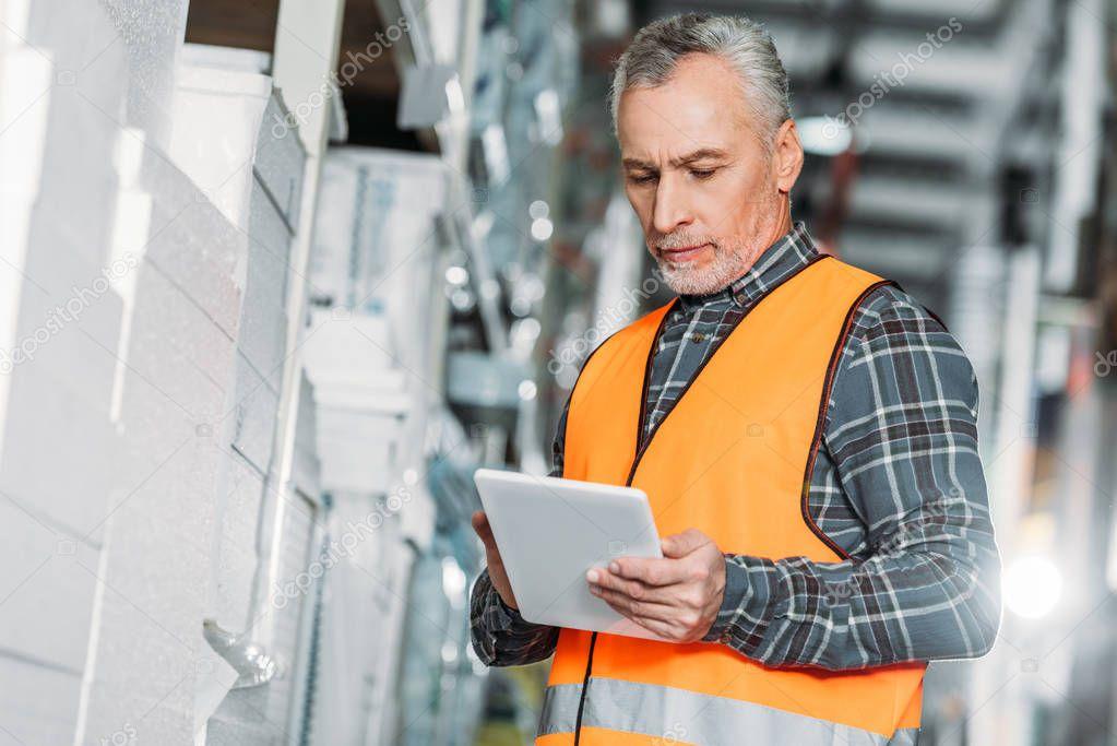 Senior worker in safety vest using digital tablet in storehouse stock vector