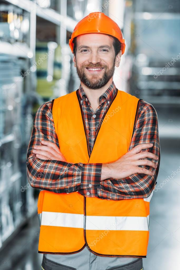 Cheerful worker in helmet and safety vest with crossed arms in warehouse stock vector
