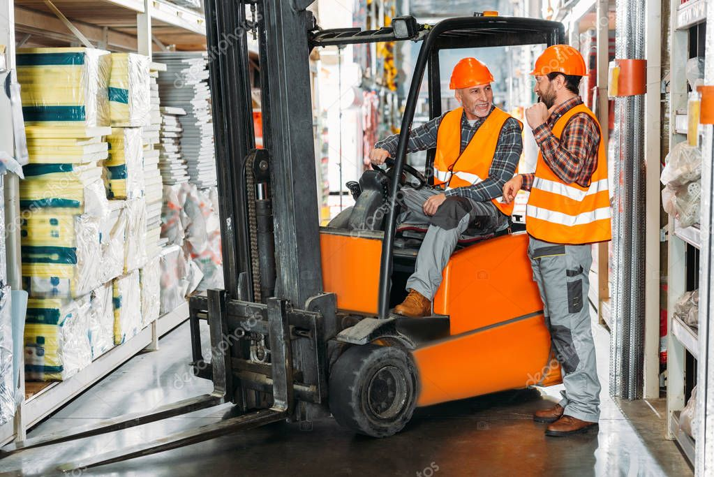 Two male workers using forklift machine in storehouse stock vector