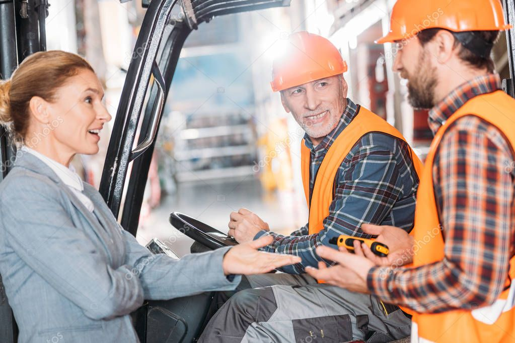 Senior worker in safety vest and helmet sitting in forklift machine and talking with colleagues in storage stock vector