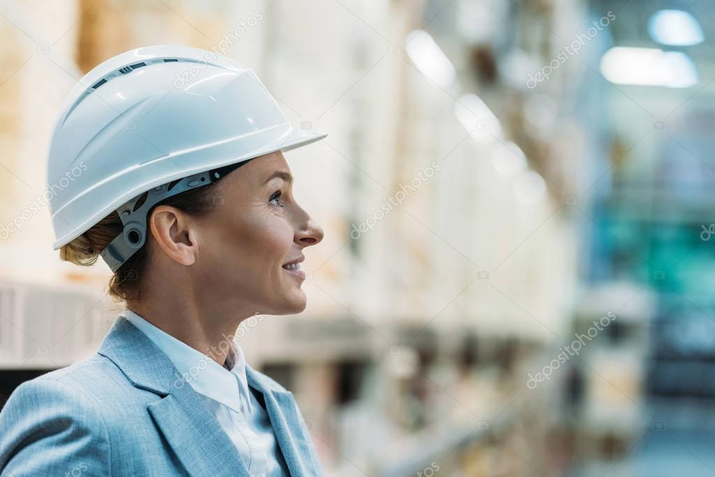 female inspector in white helmet in warehouse