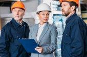 Fotografie mužských zaměstnanců v přilby a ženské inspektor s schránky ve skladu