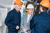 Fotografie mužských zaměstnanců a ženské inspektor v přilby ve skladu