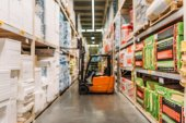 blurred view of forklift machine and shelves with boxes in storage