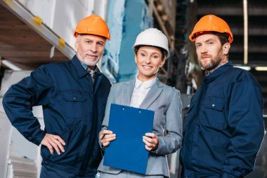male workers and female inspector in helmets in shipping stock