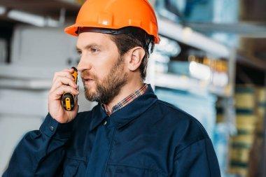 Male worker in helmet with walkie talkie in shipping stock stock vector
