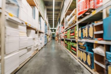 blurred view of shelves with boxes and styrofoam in warehouse