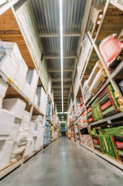 blurred view of shelves with boxes in storehouse