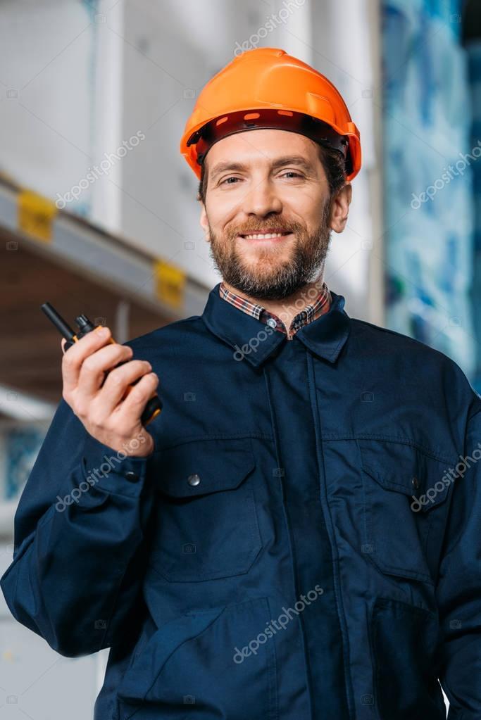 male worker in helmet with walkie talkie in shipping stock