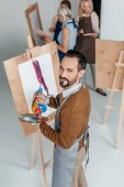 Fotografie handsome mature artist holding palette while standing near easel and smiling at camera