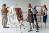a férfi és női felnőtt hallgatók kötények együtt festés, festőállványok művészeti osztályban a csoport