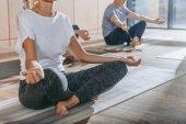 skupina starších lidí cvičí jógu instruktorem v lotosu představují na rohože ve studiu