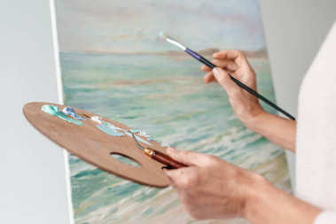 cropped shot of artist holding palette and paintbrush while painting at easel in art studio