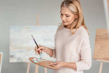 mature woman holding palette and paintbrush in art studio