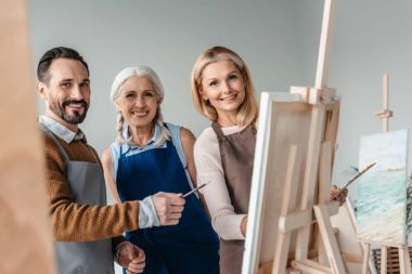 cheerful mature artists smiling at camera while painting together on art studio