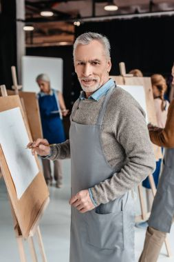 senior man smiling at camera while standing near easel at art class