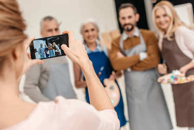 cropped shot of woman with smartphone photographing adult students of art class