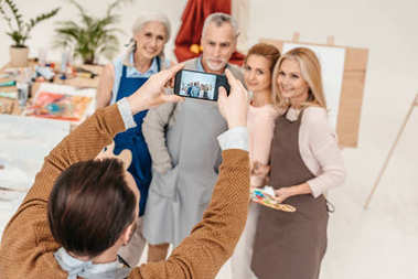 man with smartphone photographing senior students at art class