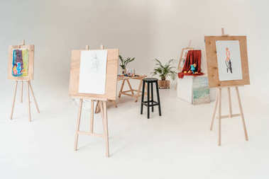 easels with paintings in empty art studio