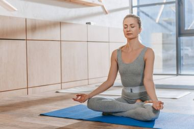 woman meditating with closed eyes in lotus yoga pose with mudra of knowledge
