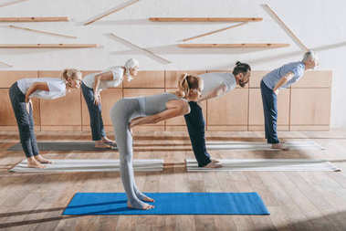 group of senior people practicing yoga with instructor on mats in studio