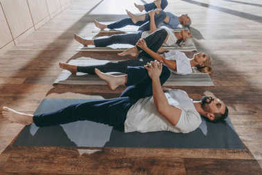 group of senior people stretching in yoga mats in studio