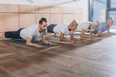 group of people doing plank on yoga mats in studio