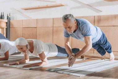 group of senior people doing plank on yoga mats in studio