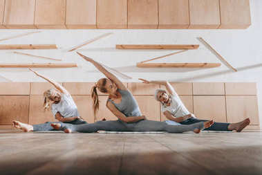 group of women stretching and practicing yoga on mats in studio