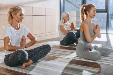 group of women meditating in lotus yoga pose with namaste mudra
