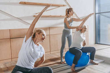 group of senior people exercising with fitness balls in studio