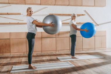 group of senior women people exercising with fitness balls in studio