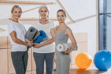 group of women holding yoga mats in studio