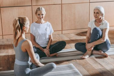 group of women sitting on yoga mats in studio