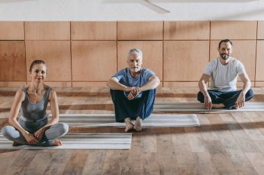 female instructor with mature men sitting on yoga mats and smiling at camera