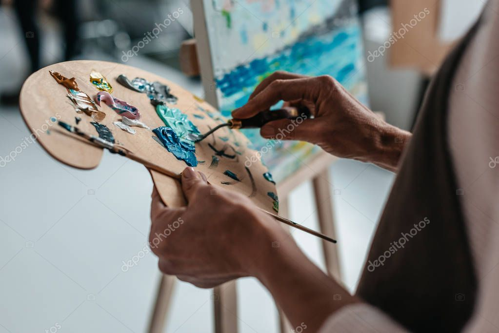 cropped shot of artist holding palette and paintbrush in art studio