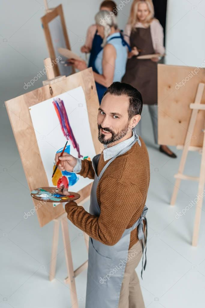 handsome mature artist holding palette while standing near easel and smiling at camera