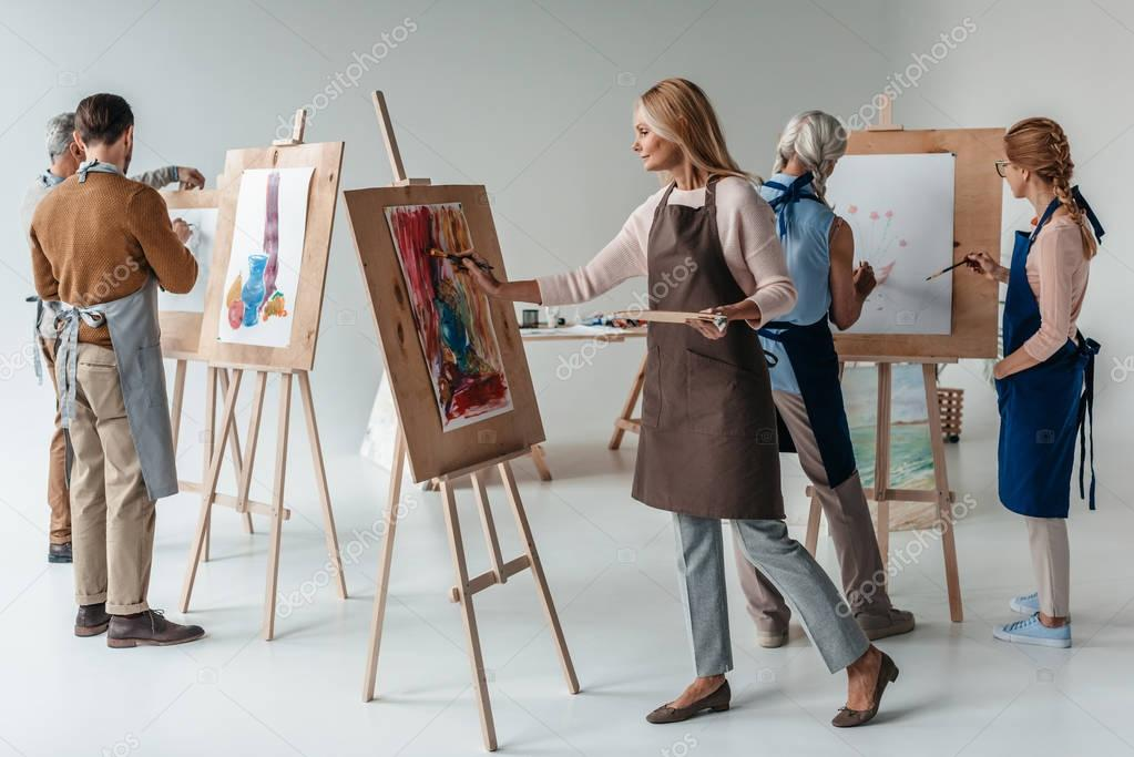 group of male and female adult students in aprons painting together on easels in art class
