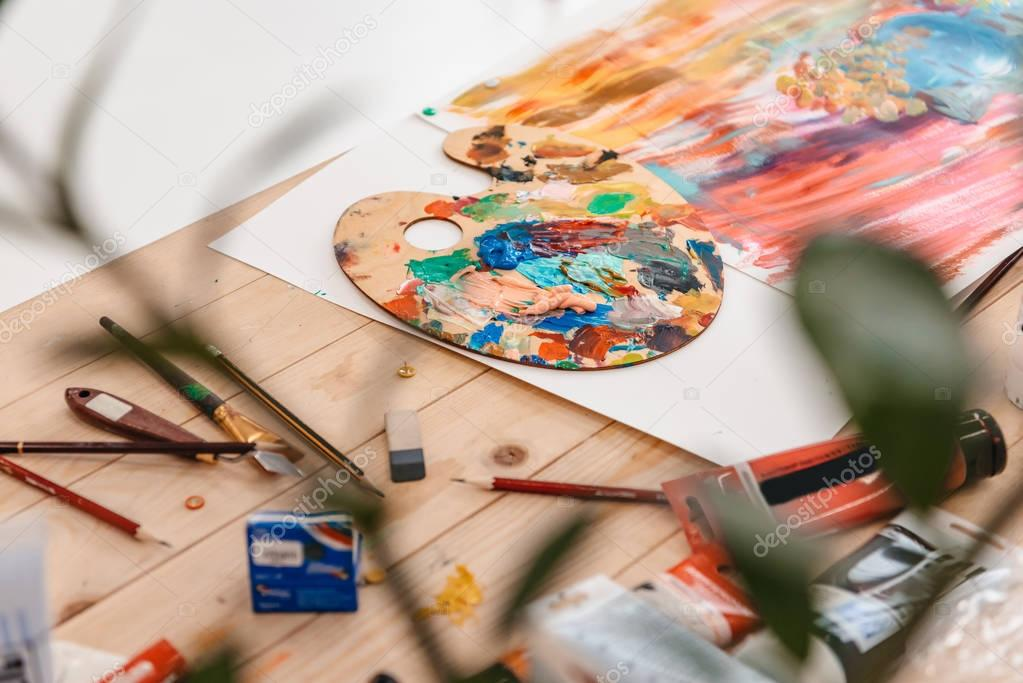 selective focus of palette with paints and art tools on table