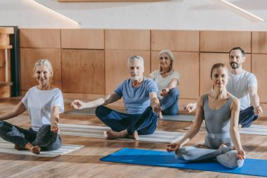 happy senior people with instructor sitting in lotus position on yoga mats