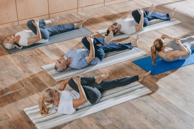 senior people with instructor stretching and exercising on yoga mats at training class