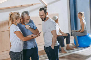 mature people looking at smartphone while training together in fitness studio