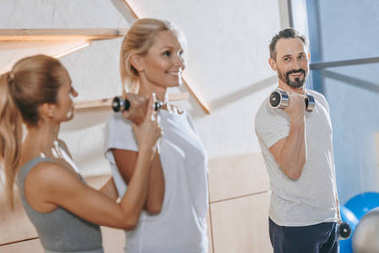 smiling mature people exercising with dumbbells and instructor helping them at training class