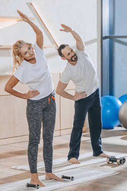mature people in sportswear exercising and looking away in fitness studio