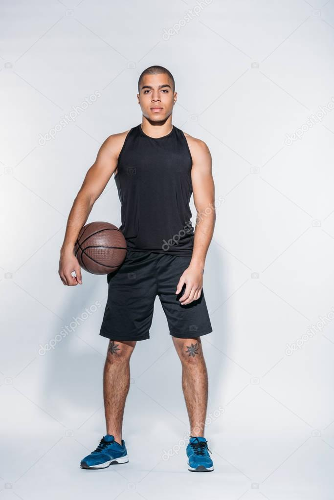 african american basketball player standing with ball