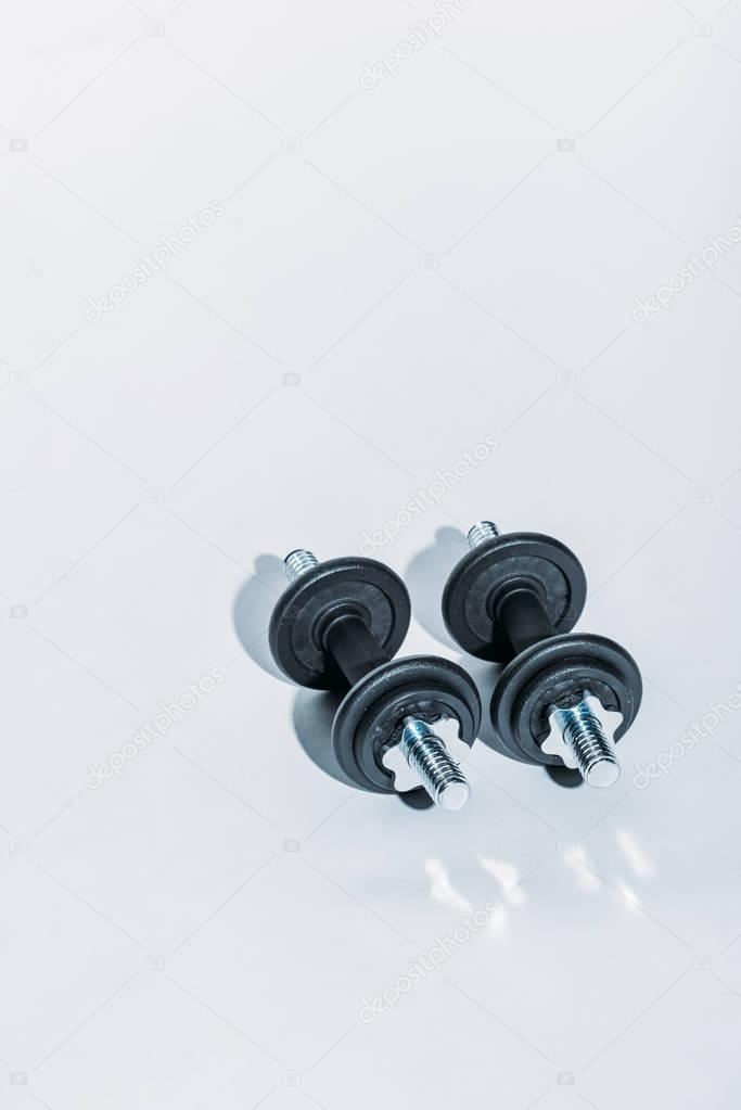 overhead view of two black dumbbells on white floor